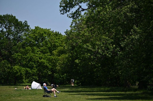 People enjoy the sunshine (Photo by JUSTIN TALLIS/AFP via Getty Images)