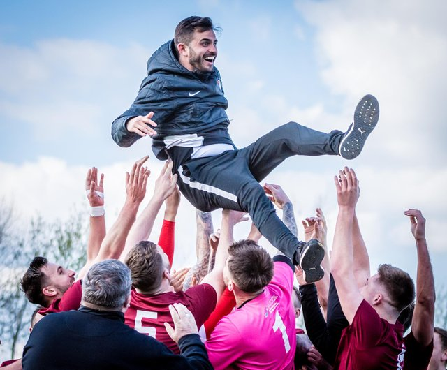 Players throw Craig Denton into the air after winning promotion.