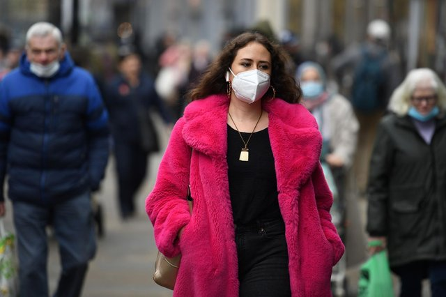 A shopper wears a facemask (Photo by OLI SCARFF/AFP via Getty Images)