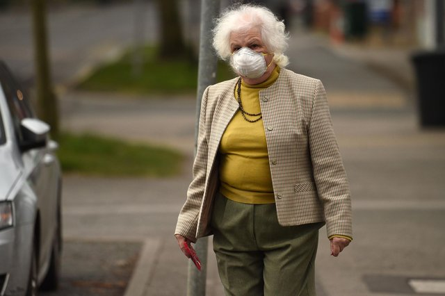 An elderly woman wearing a protective face mask leaves a newsagents (Photo by OLI SCARFF/AFP via Getty Images)