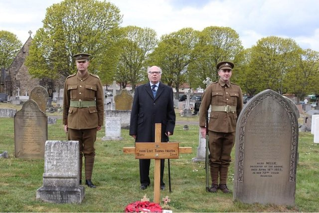 Robert Ilett standing behind the grave with the cross installed, flanked by the two men in authentic Notts and Derby Regiment uniforms of 1918.