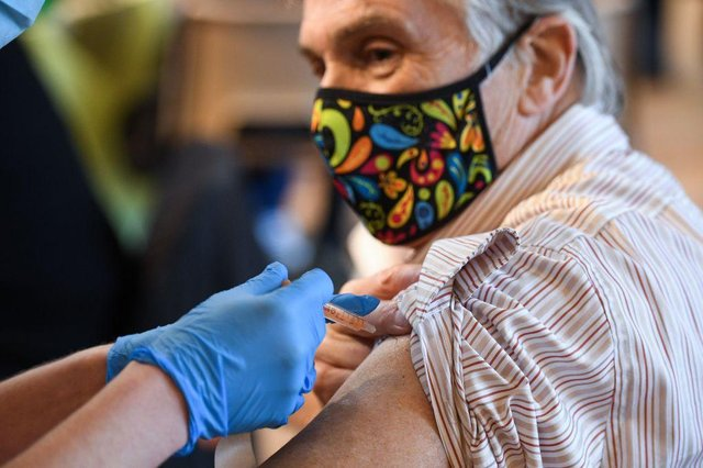 A member of the public receives the Oxford/AstraZeneca Covid-19 vaccine (Photo by OLI SCARFF/AFP via Getty Images)
