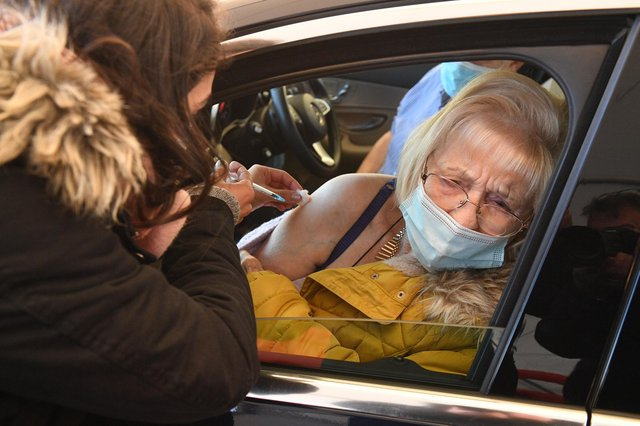 Joan Burgess receives an injection of her first dose of the Pfizer-BioNTech Covid-19 vaccine in her car at a drive-in vaccination centre in Hyde, Greater Manchester (Photo by OLI SCARFF/AFP via Getty Images)