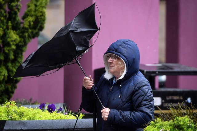 A pedestrian struggles with her umbrella against the wind (Photo by ANDY BUCHANAN/AFP via Getty Images)