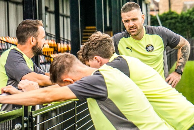 Whitehouse (behind the fence) and Jeffs talking to the players. Pic by Lewis Pickersgill.