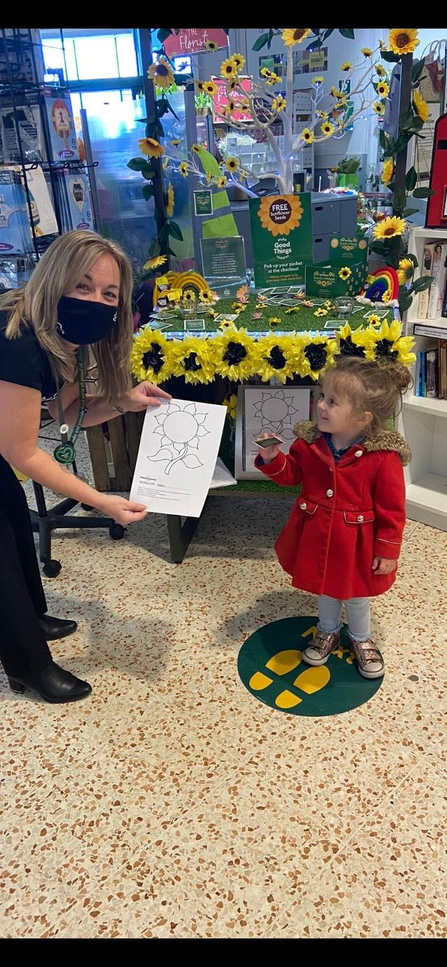 Morrison community champion Victoria Brookes handing out sunflower seeds to a young customer in Worksop