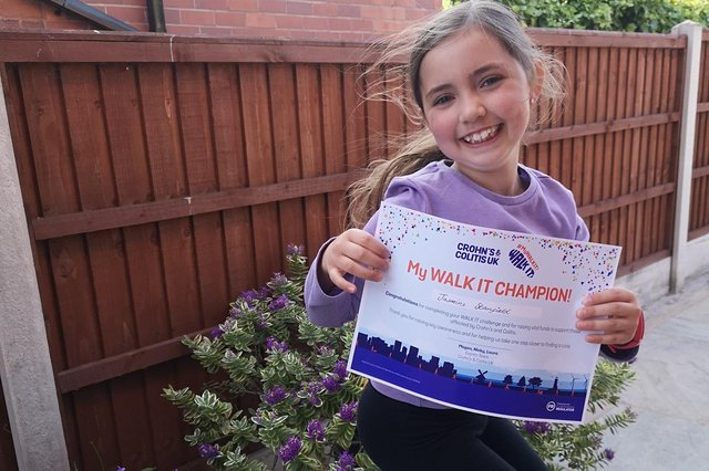 Jasmine Stanfield, seven, with her certificate for completing the Chron's and Colitis UK Walk It challenge.