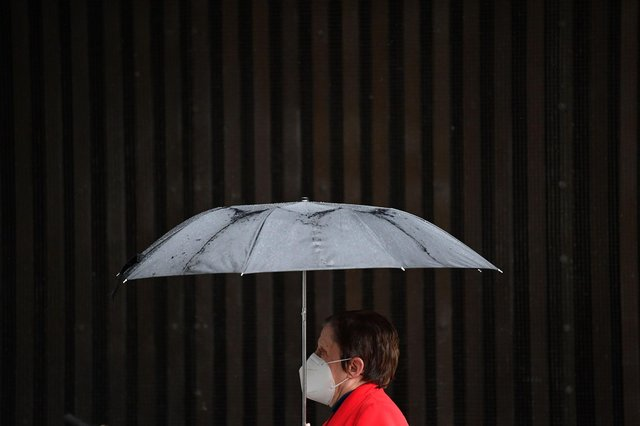 A pedestrian wearing a face mask shelters under an umbrella (Photo by JUSTIN TALLIS/AFP via Getty Images)