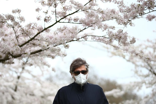 A man wearing a face mask walks amongst blossom trees (Photo by Hollie Adams/Getty Images)
