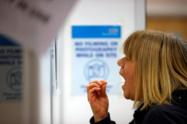 A woman uses a swab to take a sample from her mouth at a NHS Test and Trace Covid-19 testing unit (Photo by ADRIAN DENNIS / AFP) (Photo by ADRIAN DENNIS/AFP via Getty Images)