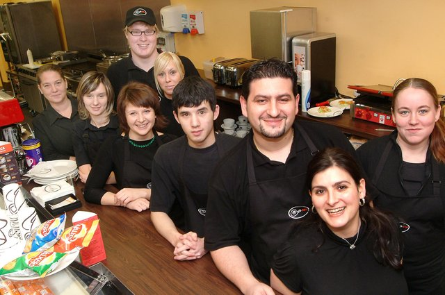 Leano Kaponas is pictured third from right with wife Diana (front) and Cafe Neo staff.