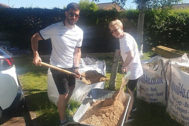 Mansfield Building Society colleagues Jen Ward and Tom Molloy work hard to fill a new sandpit with three tonnes of sand during a day of volunteering.