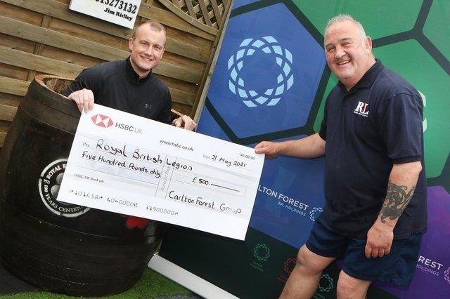 Graham White, commercial group director of Mark's main sponsors Carlton Forest Group, has his own go in the ice water and hands over a cheque for £500.