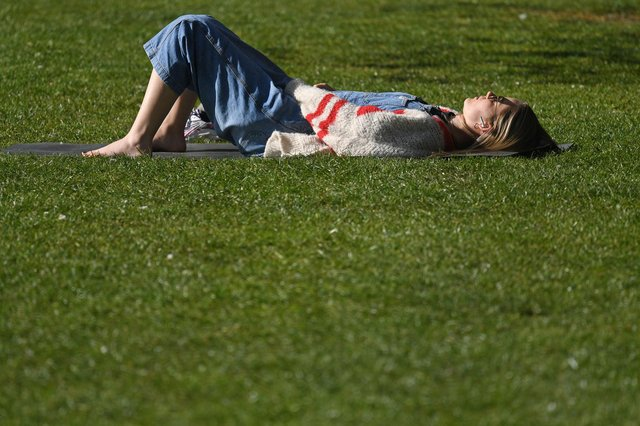 A woman sunbathes on the grass in the Spring sunshine (Photo by DANIEL LEAL-OLIVAS/AFP via Getty Images)