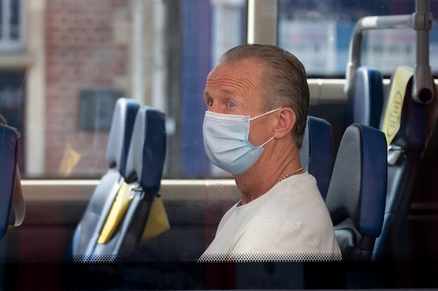 A man wears a surgical face mask on a bus (Photo by Matthew Horwood/Getty Images)